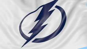 Close-up of waving flag with Tampa Bay Lightning NHL hockey team logo, seamless loop, blue background. Editorial stock video footage