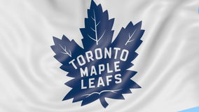 Close-up of waving flag with Toronto Maple Leafs NHL hockey team logo, seamless loop, blue background. Editorial stock video