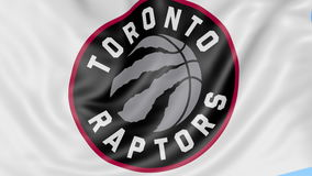 Close-up of waving flag with Toronto Raptors NBA basketball team logo, seamless loop, blue background. Editorial stock video