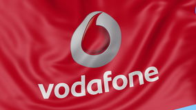 Close up of waving flag with Vodafone logo, seamless loop, blue background. Editorial animation. 4K ProRes, alpha. Close up of waving flag with Vodafone logo stock footage