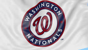 Close-up of waving flag with Washington Nationals MLB baseball team logo, seamless loop, blue background. Editorial stock video footage