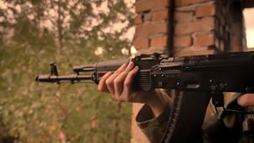 Close-up weapon shooting, caucasian soldier is looking at aim while holding gun with hands, brick abandoned house, empty. Cloudy view stock video footage