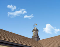 Close up of a weather vane on a roof,wind indicator, over blue sky Royalty Free Stock Image