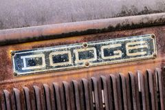 Close up of weathered Dodge truck sign. Close up of weathered and rusty Dodge sign on side of antique truck in junkyard stock image