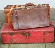 Vintage brown leather cases. A close up of a weathered vintage suitcase, leather travel bag and old red box Royalty Free Stock Images