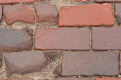 Close up of weathred red brick paved road Royalty Free Stock Images