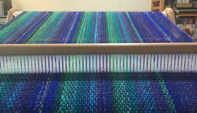 Close up of weaving on loom. Close up of colorful threads being woven into cloth on wooden loom Stock Image