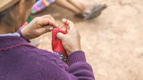 Close up of weaving in Peru. Cusco, Peru woman dressed in colorful traditional native Peruvian closing knitting a carpet with royalty free stock photos