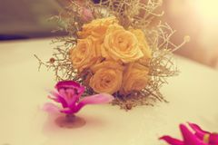 Close-up of wedding bouquet made of yellow roses on white limousine hood. Vintage tone. Stock Image
