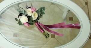 Close-up wedding bride's bouquet on glass table stock video footage