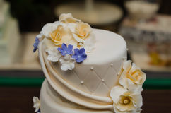 Close up wedding cake with yellow and purple flowers. Close up of a 3-tier wedding cake in the color champagne with yellow-golden and purple flowers Royalty Free Stock Photography