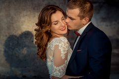 Close-up wedding portrait. The groom is tenderly kissing the charming happy ginger hair bride in the cheek. Close-up wedding portrait. The groom is tenderly Stock Photo