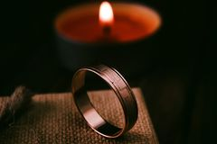 Wedding ring and burning candle background Stock Photography