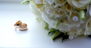 Close up of wedding ring on vintage wooden table with white rose stock video footage