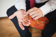 Close up wedding rings in groom hands. The wedding morning of a bridegroom Royalty Free Stock Photo