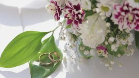Close up Wedding rings , White roses and lilac flowers . Wedding Fresh bouquet. Summer Background Video HD stock video footage