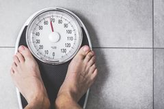 Close-up Weighing Scale ,Men standing on weigh scales. stock photo