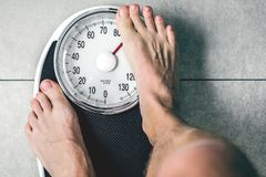 Close-up Weighing Scale ,Men standing on weigh scales. Close-up Weighing Scale ,Men standing on weigh scales royalty free stock image