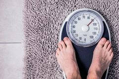 Close-up Weighing Scale ,Men standing on weigh scales. Close-up Weighing Scale ,Men standing on weigh scales stock photo