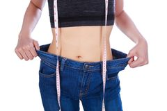 Close up weight loss woman wearing her old jeans and measure tap. E isolated on a white background Royalty Free Stock Images