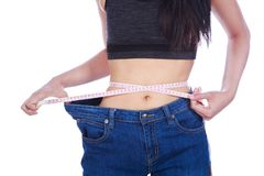 Close up weight loss woman wearing her old jeans and measure tap. E isolated on a white background Stock Photography