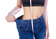 Close up weight loss woman wearing her old jeans and measure tap. E isolated on a white background Royalty Free Stock Image