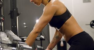 Close-up of dedicated woman training and lifting weights in fitness gym. Close-up of weights training woman in fitness gym lifting weights and showing strong stock video footage