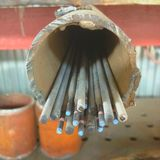 Electrodes are placed in a piece of rusty pipe in the welding shop stock photography