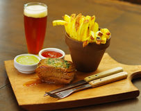 Close up of a well-done grilled marinated beef flank steak with ketchup, mustard and french fries with a glass of beer. And a kitchen untensils on wooden board stock photos