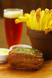 Close up of a well-done grilled marinated beef flank steak with ketchup, mustard and french fries with a glass of beer. Behind on wooden board stock photos