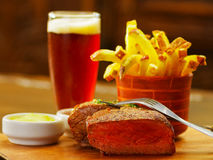 Close up of a well-done grilled marinated beef flank steak with ketchup, mustard and french fries with a glass of beer. With a fork over the meat on wooden stock images