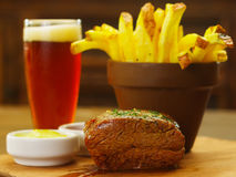 Close up of a well-done grilled marinated beef flank steak with ketchup, mustard and french fries with a glass of beer. On wooden board stock photography