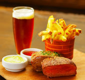 Close up of a well-done grilled marinated beef flank steak with ketchup, mustard and french fries with a glass of beer. On wooden board stock photos