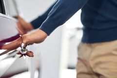 Man holding his hands on door handle and opening it. Close up of well maintained male hand in blue sweater near car`s front door. Man holding hands on door royalty free stock images