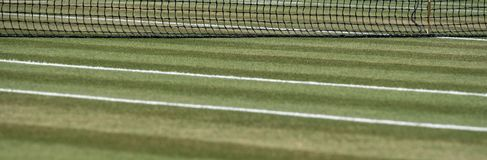 Close up of well manicured grass tennis court with net in the background at Wimbledon, London UK. Close up of well manicured grass tennis court with net in the royalty free stock photos