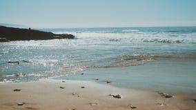 Close - up of wet Beach sand drying after waves, view of sea waves breaking on sandy coastline, deep blue ocean water