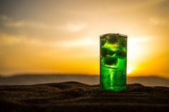 Close up wet glass of green cold mint drink, colorful orange sunset background on the terrace. Cooling summer drink. Summer fresh stock image