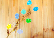 Close-up of wheat and colorful paper eggs silhouette frames against wooden background.  Stock Image