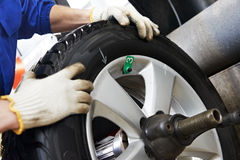 Close-up of wheel balancing. Close-up of mechanic repairman hands during balancing automobile car wheel on balancer Royalty Free Stock Photography