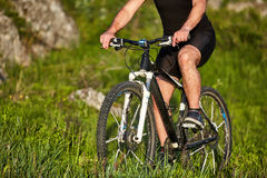 Close-up of the wheel of a bicycle and legs of the cyclist on the meadow. Stock Photos
