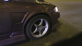 Close-up of wheel and body of shiny car. Action. Design coating of car with gold sequins sparkling in light of night. Lights of city road stock footage