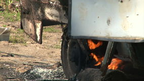 Close up of wheel burning car. Old burning car emitting smoke in an empty summer green field stock footage