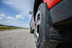 Close up of wheel of the car on dirt road at sunny spring day. View from the road Royalty Free Stock Photography