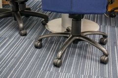 Close up wheel of office chairs on the floor. In workplace stock images