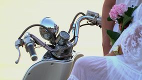 Close up of a wheel of the white moped. The woman with the man sit on the seashore. A big close-knit family have a rest. On this video you can see as the close stock video