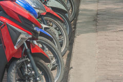 Close up wheels of many motorcycle parking on parking lot. Stock Image