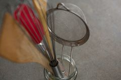 Whisker, wooden spoon, strainer and spatula on glass jar. Close-up of whisker, wooden spoon, strainer and spatula on jar stock photos