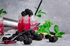 Close-up of whiskey glass of berry pink cocktail and a metal shaker. Beverage with mint, lemon and blackberries on a Royalty Free Stock Photos