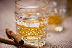 Close-up of whiskey glass on the rocks with cigars and vintage background Stock Image