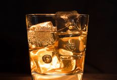 Close-up of whiskey with ice cubes in glass on dark background a Royalty Free Stock Photography